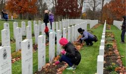 School aged child placing a single poppy on the grave of a Canadian Armed Forces Member